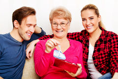 Happy family - couple with old woman who holding gift box and baby shoe Stock Image