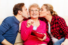 Happy family - couple with old woman who holding gift box and baby shoe Royalty Free Stock Image