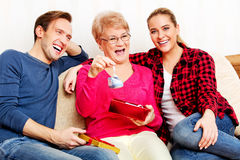 Happy family - couple with old woman who holding gift box and baby shoe Stock Photo
