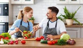 Happy family couple preparing vegetable salad in kitchen Stock Photos