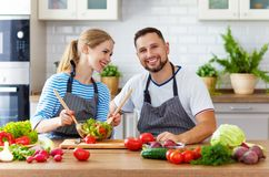 Happy family couple preparing vegetable salad in kitchen Royalty Free Stock Photos