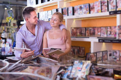 Happy  family couple selecting erotic video and smiling Stock Photos