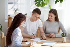 Happy family couple sign contract buying house meeting realtor. Happy family couple sign contract sale purchase agreement meeting realtor insurer broker advisor stock photos
