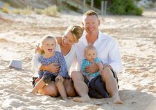 Happy family couple sitting on beach sand with baby boy son and daughter Stock Photos