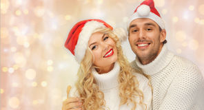 Happy family couple in sweaters and santa hats Royalty Free Stock Images