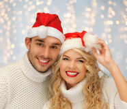 Happy family couple in sweaters and santa hats Royalty Free Stock Photos