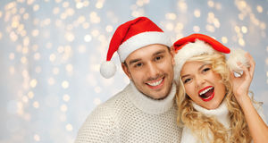 Happy family couple in sweaters and santa hats Stock Images