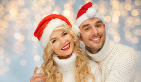 Happy family couple in sweaters and santa hats Royalty Free Stock Photography