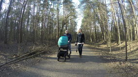 Happy family couple walk with baby carriage in spring forest. 4K stock footage