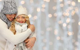 Happy family couple in winter clothes hugging. People, christmas, holidays and new year concept - happy family couple in winter clothes hugging over lights Stock Photo