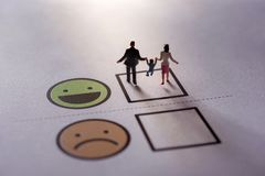Happy Family Customer Concept. present by Miniature Figure of Fa. Ther, Mother and Son in Happiness Moment. Walking on a Checked Box of Smiley Cartoon Face royalty free stock photos