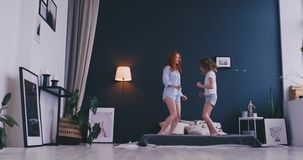 Happy family of cute daughter and young mother jumping and dancing on bed while have fun during morning on holidays at. Home stock footage