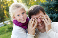 Happy family - Cute girl covers her dad's eyes while playing at Royalty Free Stock Images