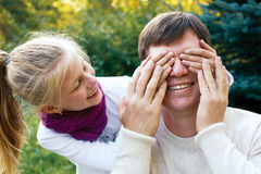 Happy family - Cute girl covers her dad's eyes while playing at Royalty Free Stock Photography