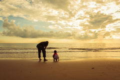 Happy family cute little boy ans dad play on beach. Sunrise background Royalty Free Stock Image