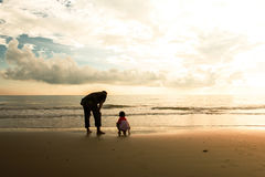 Happy family cute little boy ans dad play on beach. Sunrise background Stock Photo