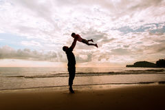 Happy family cute little boy ans dad play on beach. Sunrise background Stock Images