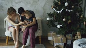 Happy family with cute little daughter sitting near Christmas tree and using smartphone at home. Happy family with cute little daughter sitting on couch near stock footage