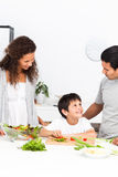 Happy family cutting vegetables together Stock Photo