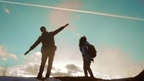 Happy family dad with daughter teamwork tourists silhouette concept. slow motion video. dad and daughter with backpacks. Show hand gesture plane journey stock video footage