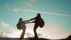 Happy family dad with daughter teamwork tourists silhouette concept. Slow motion video. Dad and daughter with backpacks. Spinning holding hands. Man lifestyle stock footage