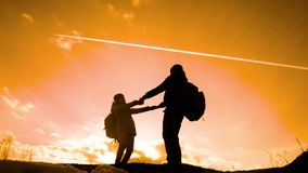 Happy family dad with daughter teamwork tourists silhouette concept. Slow motion video. Dad and daughter with backpacks. Spinning holding hands. Man and young stock footage