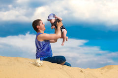 Happy family, dad and little son in striped vests having fun  in. The sand outdoors against blue sky background. Summer vacations concept. Father's day Stock Images