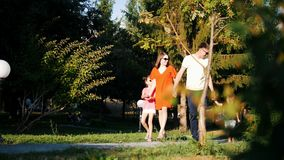 Happy family: dad, mom, daughter and son walk in the park on a sunny summer day stock footage