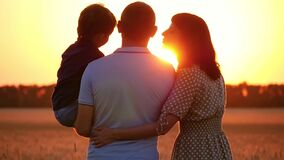 Happy family: dad, mom and little son enjoy nature and sunset. A father holds his son in his arms, a woman kisses a man stock video