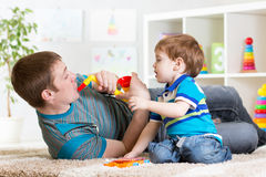 Happy family dad and son play musical toys. On floor royalty free stock image
