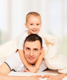Happy family. Dad and son playing in bed Stock Image