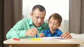 Happy family: dad and son spend time together. Father and son draw colored felt pen. Lifestyle, relationships, children stock video footage