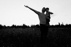 Happy family dad and son walking in spring field. Father pointing to sky royalty free stock photography