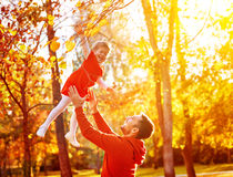 Happy family Dad throws child daughter up on walk in autumn Royalty Free Stock Photo