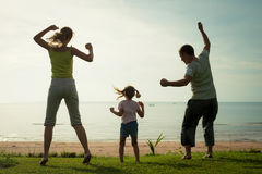 Happy family dancing the beach Stock Image