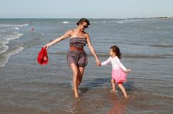 Happy family dancing at sea. Happy family mom and child dancing at sea stock photos