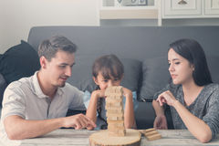 Happy family and Daughter playing the wooden blocks tower at hom Stock Photos