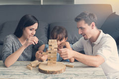 Happy family and Daughter playing the wooden blocks tower at hom Stock Images