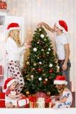 Happy family decorates Christmas pine Stock Photography