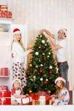 Happy family decorates Christmas pine Royalty Free Stock Photos