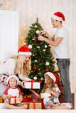 Happy family decorates Christmas pine Royalty Free Stock Image