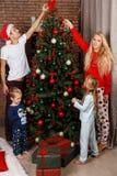 Happy family decorates Christmas pine Stock Photo
