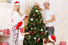 Happy family decorates Christmas pine Royalty Free Stock Images
