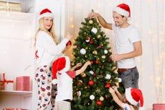 Happy family decorates Christmas pine Royalty Free Stock Photo