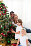 Happy family decorating a Christmas tree Stock Photography