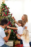 Happy family decorating Christmas tree Royalty Free Stock Image