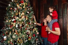 Happy family decorating a Christmas tree with boubles in the living-room. Royalty Free Stock Images