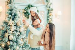 Family decorating a Christmas tree. Happy family decorating a Christmas tree with boubles in the living-room Royalty Free Stock Image