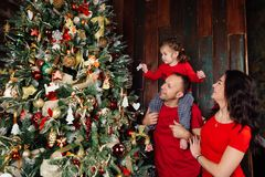 Happy family decorating a Christmas tree with boubles in the living-room. Happy family decorating a Christmas tree with boubles at home. Dad and Mom and Royalty Free Stock Images