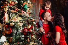 Happy family decorating a Christmas tree with boubles in the living-room. Happy family decorating a Christmas tree with boubles at home. Dad and Mom and Royalty Free Stock Photos